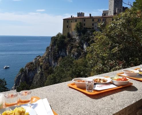 Pokud je člověk dostatečně rychlý, může si vychutnat jídlo na tomhle VIP balkóně s výhledem na Catello di Duino.